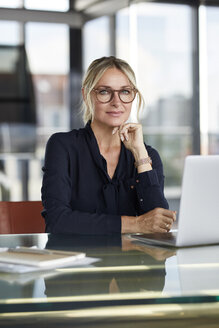 Businesswoman working in office, using laptop - RBF06642