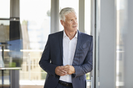 Worried businessman standing by window, thinking - RBF06663
