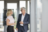 Businessman and woman standing in office, discussing project - RBF06675