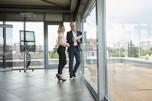Businessman and woman standing in office, discussing project, holding documents - RBF06678