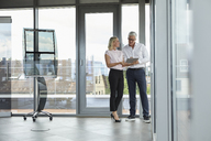 Businessman and woman standing in office, discussing project, looking at digital tabet - RBF06681