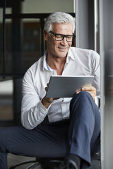 Serene businessman sitting on ground in office, using digital tablet - RBF06690