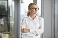 Businesswoman in office leaning against window, with arms crossed - RBF06696