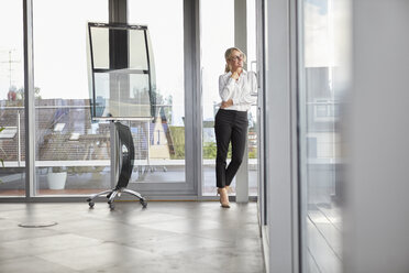 Successful businessman standing in office, looking out of window - RBF06699