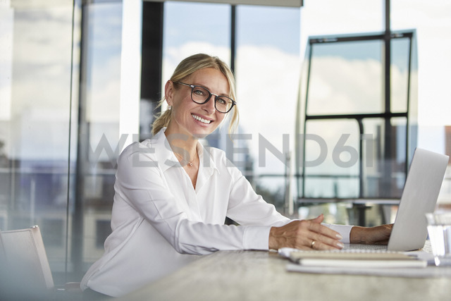 Businesswoman sitting at desk, using laptop, smiling friendly - RBF06705 - Rainer Berg/Westend61