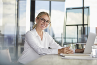 Businesswoman sitting at desk, using laptop, smiling friendly - RBF06705