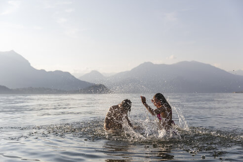 Happy young couple playing in a lake - MRAF00275