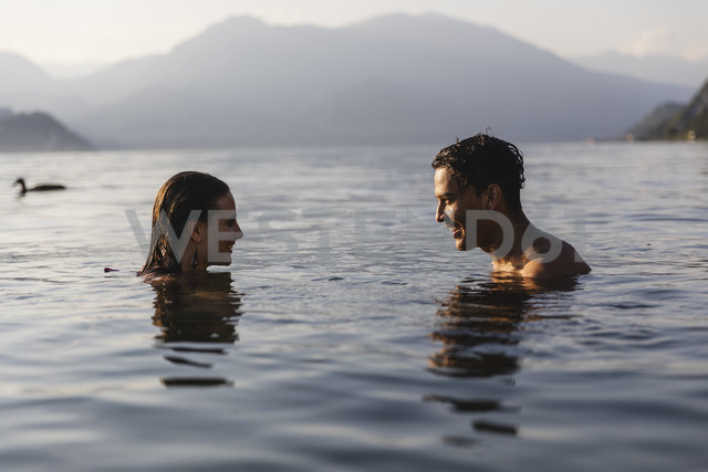 Happy young couple in a lake smiling at each other - MRAF00281 - Michela Ravasio/Westend61