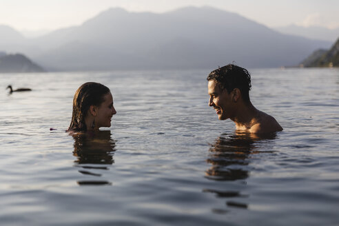 Happy young couple in a lake smiling at each other - MRAF00281