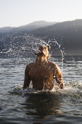 Young man tossing his hair in a lake - MRAF00293