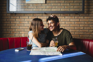 Happy young couple sitting at table in a cafe with map - MRAF00326