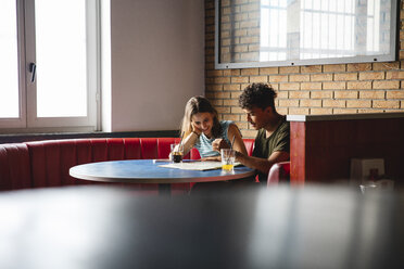 Young couple sitting at table in a cafe with map - MRAF00329