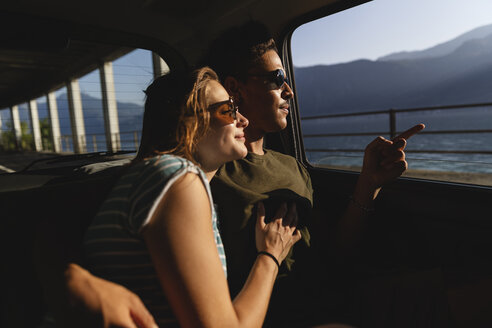 Affectionate young couple sitting in a car looking out of window - MRAF00335