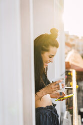 Happy young woman on balcony above the city at sunset holding cell phone and cup of tea - KKAF01837