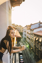 Beautiful young woman on balcony above the city at sunset with cup of coffee - KKAF01840