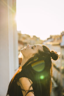 Beautiful young woman on balcony above the city at sunset - KKAF01843