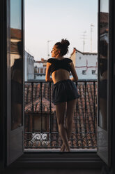 Beautiful young woman standing on balcony at sunset - KKAF01846