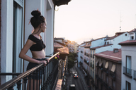 Beautiful young woman on balcony above the city at sunset - KKAF01849