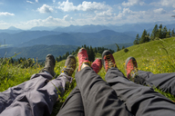 Germany, Bavaria, Brauneck near Lenggries, legs of hikers in meadow in alpine landscape - LBF02070