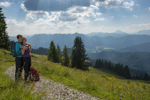 Germany, Bavaria, Brauneck near Lenggries, happy young couple having a break looking at view in alpine landscape - LBF02073