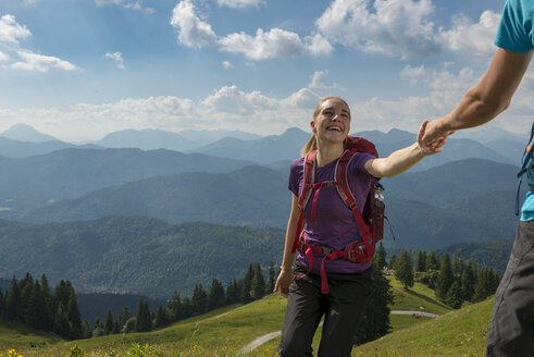 Germany, Bavaria, Brauneck near Lenggries, happy young woman hiking in alpine landscape holding hand of boyfriend - LBF02079