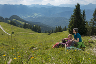 Germany, Bavaria, Brauneck near Lenggries, happy young couple having a break sitting in meadow in alpine landscape - LBF02085