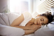 Portrait of young woman sleeping in bed at day - ABIF01008