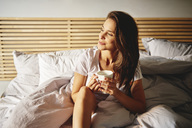 Portrait of smiling young woman sitting on bed with cup of coffee looking at distance - ABIF01014