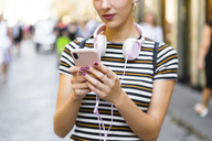 Woman using smartphone on the street, partial view - MGIF00248