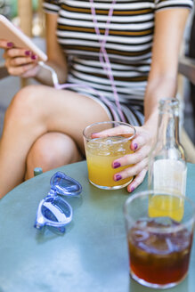 Young woman sitting at pavement cafe enjoying soft drinks, partial view - MGIF00254