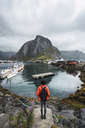 Norway, Lofoten, rear view of man standing at the coast - KKAF01861