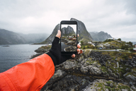 Norway, Lofoten, man's hand taking cell phone picture at the coast - KKAF01864