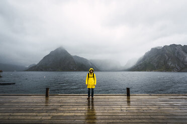 Norway, Lofoten, man standing on a pier at the coast - KKAF01870