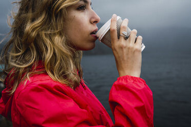 Norway, Lofoten, young woman at the coast drinking from takeaway coffee - KKAF01879