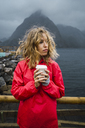 Norway, Lofoten, young woman at the coast holding takeaway coffee - KKAF01882