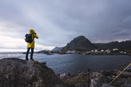 Norway, Lofoten, rear view of man standing on a rock at the coast taking a picture - KKAF01885