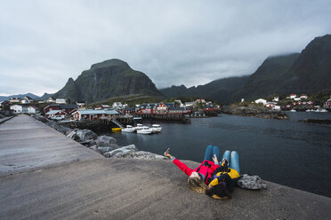 Norway, Lofoten, two young women lying on a pier at the coast taking a selfie - KKAF01888