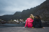 Norway, Lofoten, rear view of two young women sitting on a pier at the coast - KKAF01891