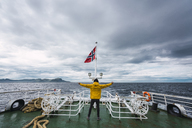 Norway, Senja island, rear view of man standing on ship deck with outstretched arms - KKAF01903
