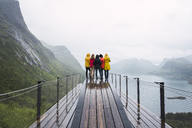 Norway, Senja island, rear view of friends standing on an observation deck at the coast - KKAF01906