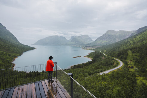 Norway, Senja island, rear view of man standing on an observation deck at the coast - KKAF01909
