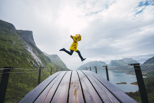 Norway, Senja island, man jumping on an observation deck at the coast - KKAF01912