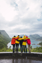 Norway, Senja island, rear view of friends embracing on an observation point at the coast - KKAF01915