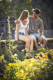 Romantic young couple sitting on wall in a park, with arms around - SRYF00787