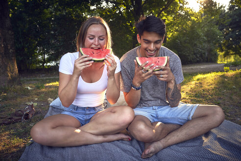 Young couple sitting in park, eating watermelon - SRYF00811