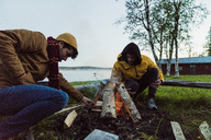 Sweden, Lapland, Two friends preparing a bonfire at the lakeshore - KKAF01926