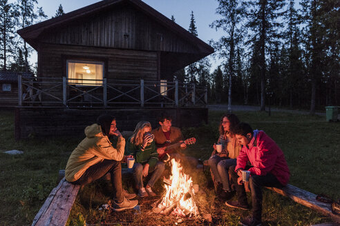 Group of friends sitting at a campfire, talking and playing guitar - KKAF01944