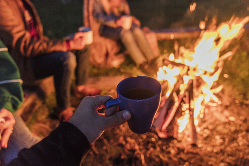 Hand of person holding tea cup, group of people sitting at a camp fire - KKAF01950