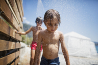 Portait of little boy having shower on the beach - AZOF00027