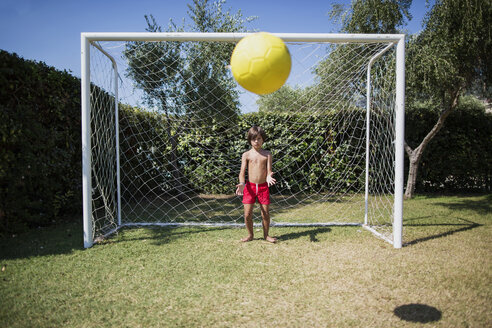 Little boy standing in front of soccer goal watching football - AZOF00036